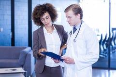 Doktor und Kollege, die ärztlichen Attest betrachten stockbilder