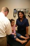Doktor und Krankenschwester überprüfen jungen Patienten Lizenzfreie Stockfotografie