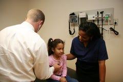 Doktor und Krankenschwester überprüfen jungen Patienten lizenzfreie stockbilder