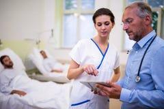Doktor und Krankenschwester, die über digitaler Tablette sich besprechen lizenzfreie stockfotos