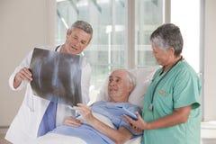 Doktor und Krankenschwester mit Patienten Stockbild