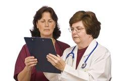 Doktor und Krankenschwester Review Patient Records Stockfotos