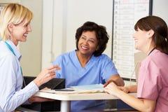 Doktor und Krankenschwestern in der Diskussion an der Krankenschwester-Station Lizenzfreie Stockfotos