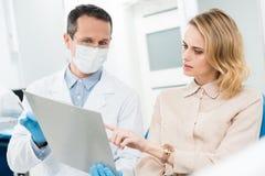 Doktor und lächelnder Patient, die Diagnosenaufzeichnungen in modernem betrachten lizenzfreie stockfotografie