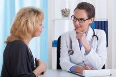 Doktor und Mitte gealterter Patient Stockbild
