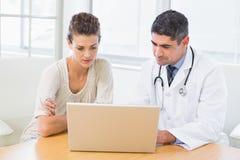 Doktor und Patient, der Laptop im Ärztlichen Dienst verwendet lizenzfreies stockbild