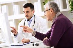 Doktor und Patient, die auf Computer zeigen lizenzfreie stockfotos