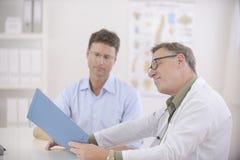 Doktor und Patient, die Blutprüfung Resultate behandeln Stockfoto