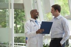 Doktor und Patient, die Krankenblatt im Krankenhaus lächeln und besprechen Stockbild
