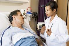 Doktor und Patient, die miteinander sprechen Stockbilder