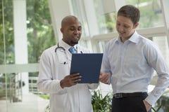 Doktor und Patient, die unten schauen und Krankenblatt im Krankenhaus besprechen Lizenzfreie Stockfotografie