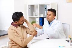 Doktor und Patient mit Armverletzung am Krankenhaus Stockfoto