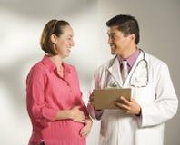 Doktor und schwangere Frau. Lizenzfreie Stockbilder
