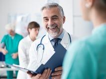 Doktor undersökande sjukdomshistorier för patient` ett s arkivbild