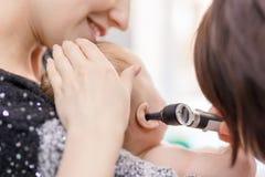 Doktor Untersuchungschilds Ohr mit Otoscope Mutter, die Baby mit den Händen hält Kindergesundheitswesen und Krankheitsverhinderun lizenzfreie stockfotos