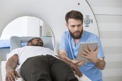 Doktor Using Digital Tablet durch den Patienten, der auf CT-Scanner liegt Lizenzfreie Stockfotos