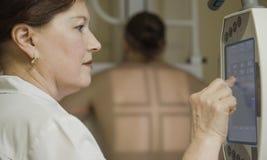 Doktor verweist Röntgenmaschine auf einem Patienten Lizenzfreie Stockfotografie
