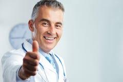 Doktor von mittlerem Alter, der sich Daumen zeigt Lizenzfreie Stockfotos