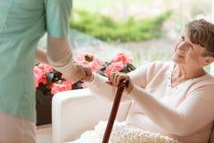 Doktor, welche einer älteren Frau mit Parkinson-` s Krankheit hilft, stehen auf lizenzfreie stockfotografie
