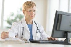 Doktor Working On Computer på skrivbordet Arkivfoto