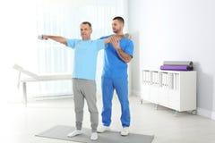 Doktor Working med patienten Rehabiliteringövningar arkivfoto