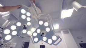 Doktor zeichnet zusammen zwei chirurgische Lampen in einem medizinischen Raum stock video footage