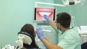 Doktor zeigt auf dem Monitor die gesunden Zähne des Patienten stock footage