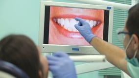 Doktor zeigt auf dem Monitor die gesunden Zähne des Patienten stock video