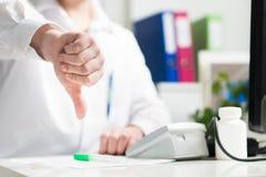 Doktor zeigt Daumen unten Trauriges oder enttäuschtes Doc., Mediziner, Krankenschwester lizenzfreies stockfoto