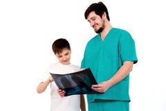 Doktor zeigt Röntgenstrahlen des Patienten auf einem weißen Hintergrund Stockfotos