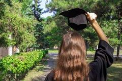 Doktorand- fira med ett lock i hennes hand och att känna sig så stolt och lyckligt i avläggande av examendag royaltyfri bild