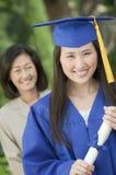 Doktorand- hållande diplom med modern bak den utvändiga ståenden Royaltyfria Bilder