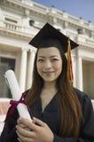 Doktorand- hållande diplom utanför universitetståenden Fotografering för Bildbyråer