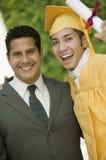 Doktorand- hissa diplom med armen runt om fader utanför ståenden Arkivbild