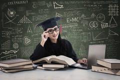Doktorand- lära för kvinnlig med bärbara datorn Arkivbild