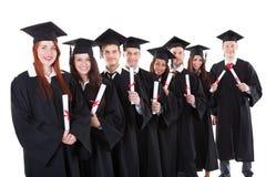 Doktorander som står i hållande diplom för rad Arkivfoto
