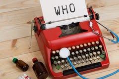 Doktorarbeitsplatz mit blauem Stethoskop, Pillen, rote Schreibmaschine mit Text WHO-Weltgesundheitsorganisation stockfotografie