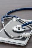 Doktorarbeitsplatz mit digitaler Tablette und Stethoskop Lizenzfreie Stockfotografie