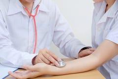 Doktorauskultation unter Verwendung Stethoskop Frauen Stockfotos