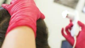 Doktordermatologe bestimmt die Struktur des Haares eines jungen hübschen Mädchens mit einem Spezialwerkzeug - ein trichoscope stock video