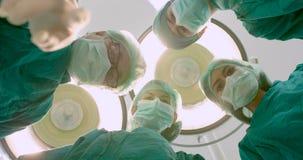 Doktoren, die den Patienten im Operationssaal betrachten stock footage
