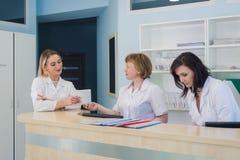 Doktoren, die Diskussionskrankenhausaufnahme während Leute sitzen im Hintergrund haben Lizenzfreies Stockfoto