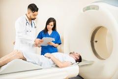 Doktoren, die eine Tomographie des Patienten nehmen lizenzfreies stockfoto