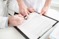 Doktoren, die einen ärztlichen Attest unterzeichnen Lizenzfreies Stockbild