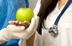 Doktoren, die einen grünen Apfel anhalten Stockfoto