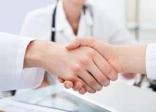 Doktoren, die Hände am Schreibtisch rütteln Stockbilder