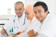 Doktoren, die im Krankenhausbüro sich besprechen Stockbild