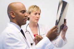 Doktoren, die Röntgenstrahl betrachten Stockbild