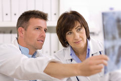 Doktoren, die Röntgenstrahlbild betrachten Stockbild