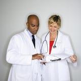 Doktoren, die Schreibarbeit lesen. Stockfotos